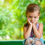 Little girl on a green lawn leans against chair and thinks of mother.